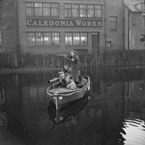Home Guards in the Edinburgh area had organised a motor boat patrol for use on the canals and waterways of the district to protect local factories and buildings. In this photograph, Home Guards patrol a section of an Edinburgh canal in a motor boat armed with rifles and a mounted Lewis gun on 19 October 1940.