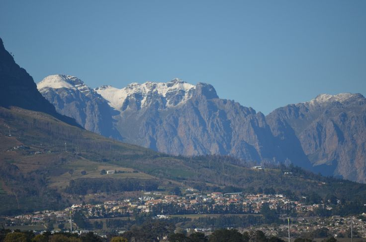 Hottentots-Holland mountain range clad in its white August scarve. Helderberg mountain to the left visible above the upper areas of the Heldervue suburb of Somerset West near Cape Town.