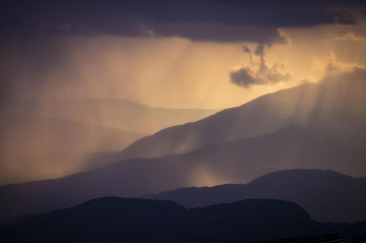 Mountain ridges and rain cloud silhouetted by setting sun, Zagóri, Greece.