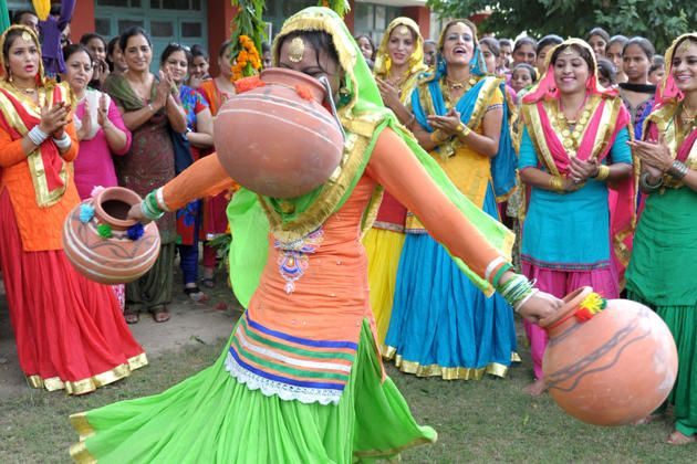 Young Indian women wearing traditional Punjabi dress look on as one dances the 'giddha' during Teej festival celebrations on the occasion of Sawan (rain) Month at Shahzada Nand College in Amritsar on August 8, 2014
