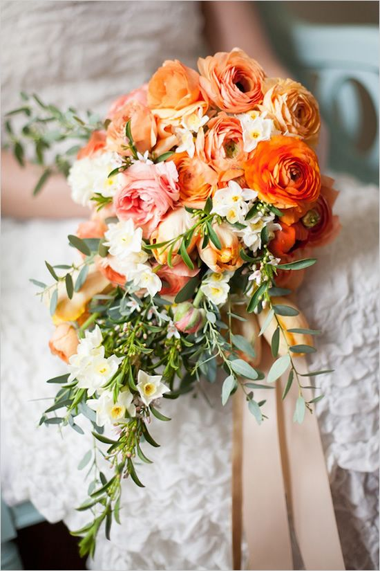 This hand tied cascade bridal bouquet is tied with gold, blush and lace ribbons. Stems of ranunculus in shades of orange, peach, coral and pink, orange and green parrot tulips, narcissus (which not only look pretty but also smell amazing), and sprigs of citrus blossom and eucalyptus were used to make this pretty bouquet