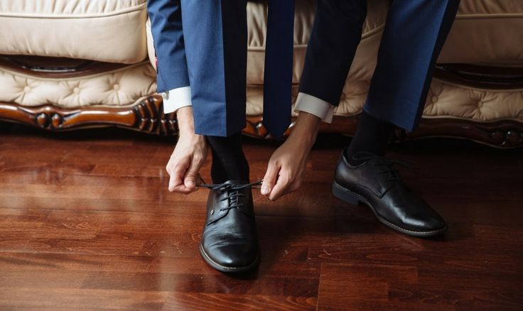 Man in blue suit tying black shoes
