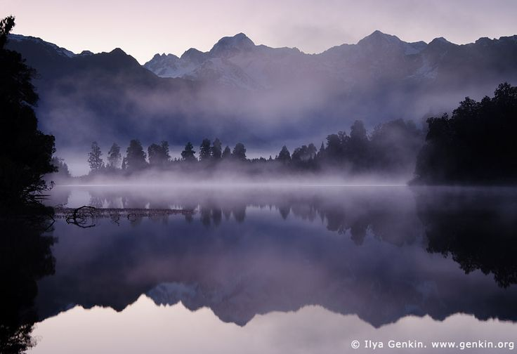 Mt Tasman and Aoraki/Mt Cook reflected in Lake Matheson, Lake Matheson, South Westland, South Island, New Zealand. Sunrise light on the Southern Alps being perfectly reflected in the calm waters of Lake Matheson near Fox Glacier. At Lake Matheson nature has combined exactly the right ingredients to create truly stunning reflections of New Zealand's highest peaks - Aoraki (Mount Cook) and Mount Tasman. New Zealand's highest mountain, Mount Cook or Aoraki (3,754m) is on the right, and Mount…