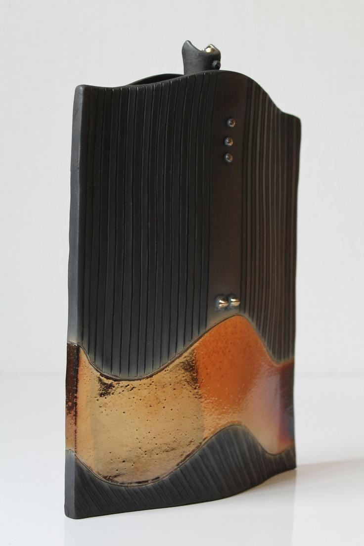 Bottiglia in ceramica in cui si la banda di color oro è messa in evidenza dal nero opaco del bucchero.