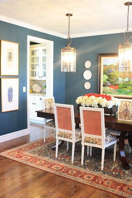 Dark blue walls (with or without white chair rail/wainscoting) would tie into blue and white accessories and make an elegant, cozy statement in the dining room and work well with your rug and artwork.