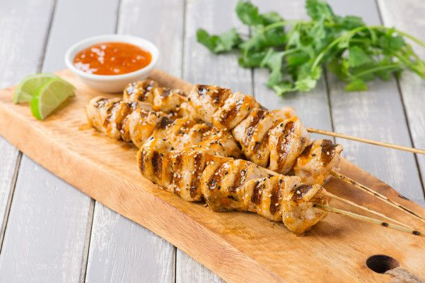 Wooden cutting board with Grilled Chicken Skewers with Sweet Asian Chill Glaze and extra sauce for dipping