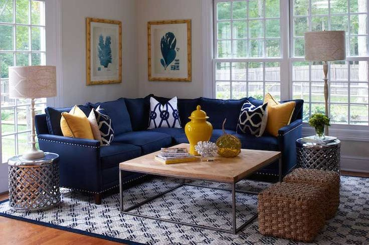 Yellow and blue living room features blue coral prints in bamboo frames over navy sectional sofa with silver nailhead trim accented with yellow pillows and white and navy geometric pillows flanked by round metal tables facing a square industrial coffee table topped with yellow urn along with seagrass cube ottomans atop white and blue geometric rug.