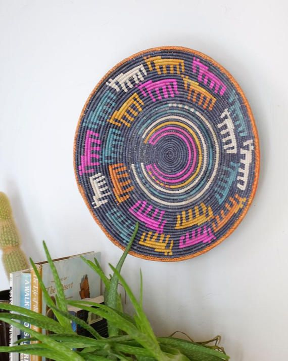 This beautiful Southwestern basket is made with extra fine coil weavings. Earthy yet vibrant, this vintage beauty adds the perfect amount of color and art to any space! Sacred weavings adorn this basket with meanings and stories behind each symbol- which makes each basket one of a kind and special.  Use for as decor, fruit bowl, or the perfect housewarming gift! Our favorite way to use these baskets is to mix and match with other southwestern baskets on a wall for 3 dimensional art…