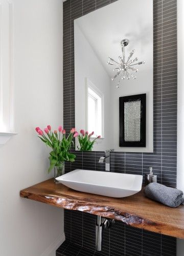 Lovely vanity design with charcoal grey bathroom tiles, organic timber bench and white drop in basin.