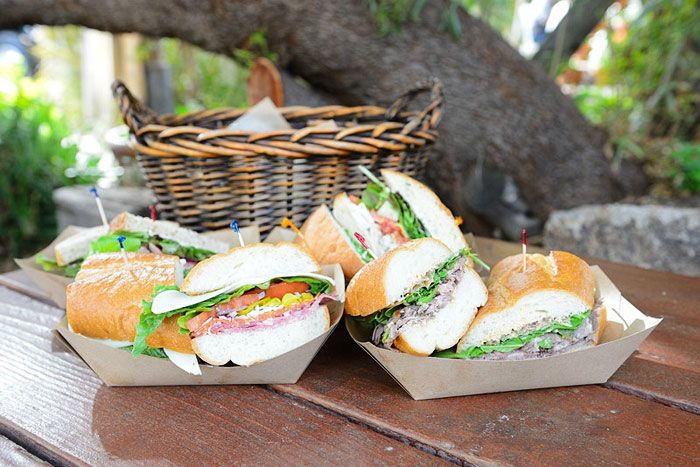 Classic roast beef sandwiches and Italian sandwiches with layered meats, shredded Parmesan Reggiano and Asiago cheeses, red onion, pepperoncini, and Farmhouse vinaigrette served on baguettes, by Santa Barbara Catering Company in Tempe, Arizona