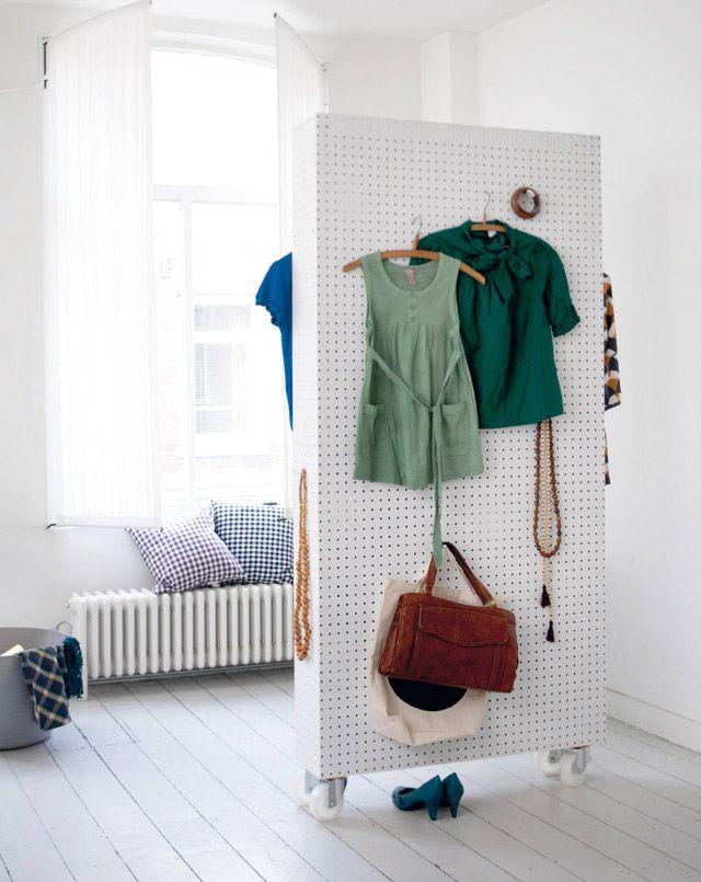 Eine Lochtafel auf Rollen dient als praktischer Raumtrenner in diesem Schlafzimmer