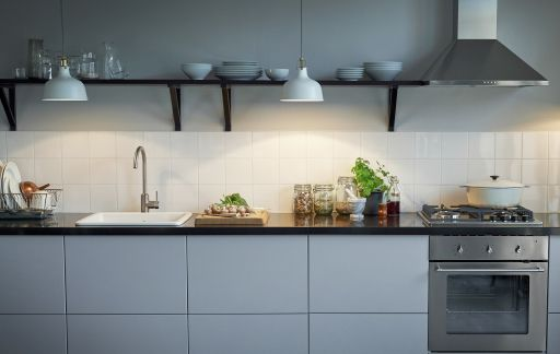 A fully functional kitchen with hanging pendant lamps.