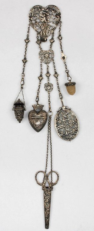 "Heart shaped plaque with reticulated repousse allegorical figures and five appendages of various origins and makers consisting of scissors and scabbard, thimble bucket, thread wax, mirror and heart shaped box. Maker's mark ""SB (obscured)"" and untraced. Plaque 2 1/2 x 8, overall L-17 3/4. Weighable silver, 4 ozt. excluding scissors, mirror and wax acorn. (Tiny crack to edge of plaque) excellent. $720"