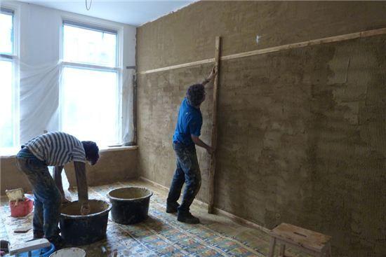 Arie maakt de muur glad op de houten latten ,1 voor de plint montage en 1 voor eventuele montage van schilderijen