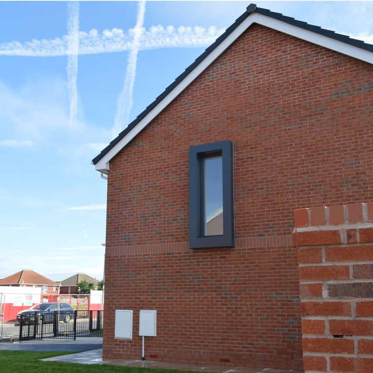 Window Lane, John McCall Architects. Red brick gable with dark grey window surround