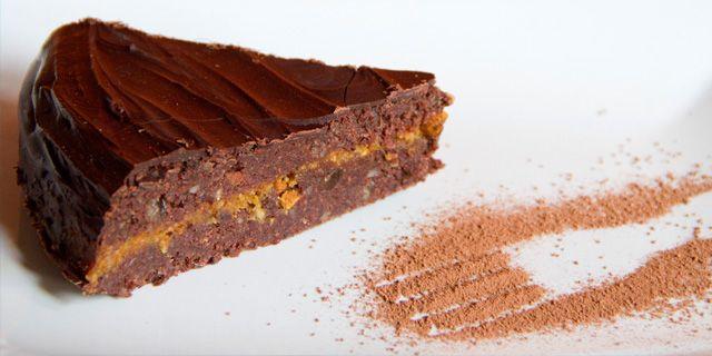 Una fetta di torta sacher crudista con composta di arance e fichi e cioccolato