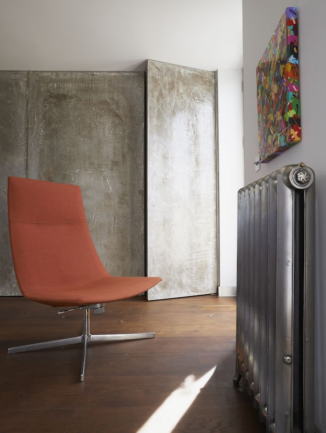 A Modern Orange Chair With Metal Base Against A Concrete Wall With A Metal  Radiator,