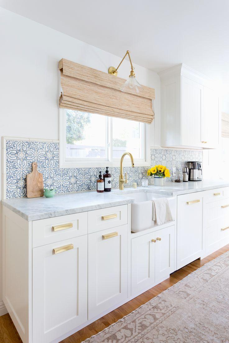 white kitchen cabinets brass hardware woven window shades modern clean bright cement tile blue
