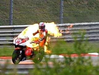 """2003 German Grand Prix. Colin Edwards narrowly escaped injury after his Aprilia RS3 Cube goes up in flames. The RS3, an in-line triple, was technically advanced but difficult to ride having a tendency to wheelie easily, a lack of front-end feel, vibration from both the front and rear wheels, and unpredictable response from its fly-by-wire throttle system. The engine was considered the most powerful at that time, producing about 240 bhp. According to Edwards, the bike was simply """"born bad."""""""