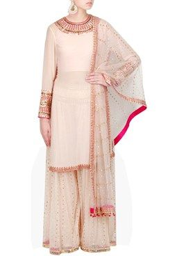Blush pink pure georgette kurta with embellished gold hand embroidery on neck and cuff . It comes with a hand embroidered blush pink net sharara and matching dupatta with fuschia highlighting .Shop Now at www.carmaonlineshop.com #carma #carmaonlineshop #designer #online #kurta #sharara #embroidery #sequins #georgette #VvanibyVaniVats #VaniVats #opulent #romanticism #shopnow