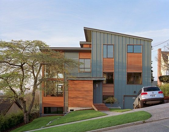 The exterior of the house is clad in low-maintenance fiber-cement siding with stained wood accents and inexpensive thermal-break aluminum windows.: