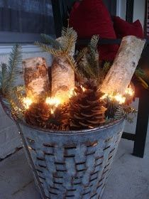 Bucket with logs, pinecones, evergreen trimmings, and Christmas or LED wire lights
