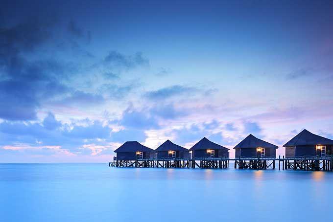Water villa cottages at sunset on island of Kuredu, Maldives