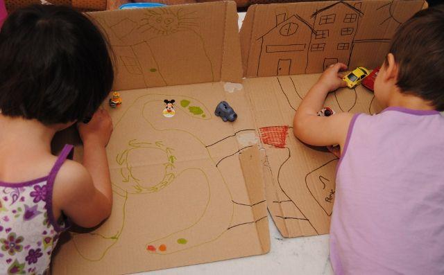 Kinderen spelen met speelstad van een kartonnen doos van melkverpakking