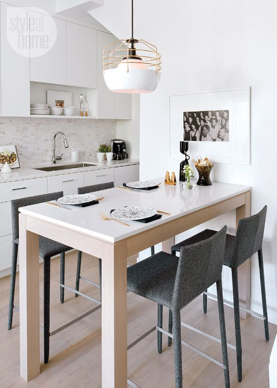 The narrow white kitchen features compact appliances that are integrated into the cabinetry. Because this is the home's only dining area, Kelly splurged on Felt Arper dining stools, which are as comfortable as they are stylish. The counter‐height dining table doubles as a food‐prep surface when not in use.