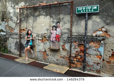 PENANG, MALAYSIA-JULY 6: Local tourist poses on Street Mural installation tittle 'Children on the Swing' painted by Louis Gan in Penang on July 6, 2013. - stock photo