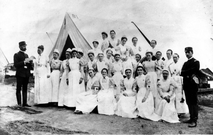 First nurses at Sternberg Hospital, Chickamauga Park, Georgia, August 1898 during the Flu epidemic. No masks or gloves, but wearing a full-length gown and apron to protect against infection, plus a new form of identification: the arm cuff with a large red cross.