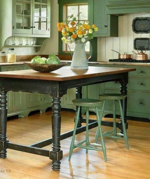 Colonial kitchen has a large table that doubles as an island.  bhg