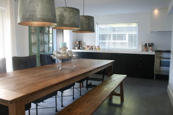 Eetkamer tafel met bijpassend bankje voor extra kontjes. Zwarte keuken met strak wit werkblad. Tafel, bankje en kappen via DHome