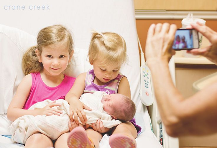 A favorite hospital newborn photo as two sisters meet their baby brother for the first