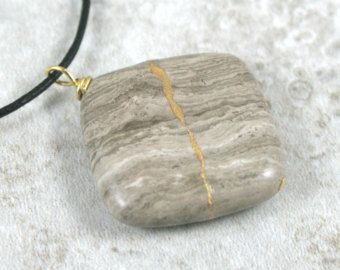 Kintsugi (ook bekend als kintsukuroi) is een Japanse kunstvorm die reparaties van gebroken aardewerk met een goud-geïnfundeerd lak te creëren van gouden naden in de gerepareerde vorm waarmee u gemakkelijker meer mooie en waardevolle dan het origineel.  In deze tegenhanger simuleren ik dit proces met behulp van een mix van gepoederde gouden mica, gouden verf en epoxy plakken om te herstellen van de pauzes in de stenen hanger te symboliseren de manier dat de genezing van de gebroken plaatsen…