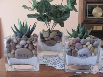 Anchor a faux plant in a base of sand, add an inscribed rock near the front and fill the remainder of the vase with mini river rocks.