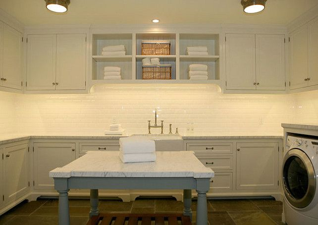 Laundry Room. white cabinets, gray laundry room island, calcutta gold counter tops, beveled subway tiles backsplash, farmhouse sink, and white washer & dryer. Giannetti Home.