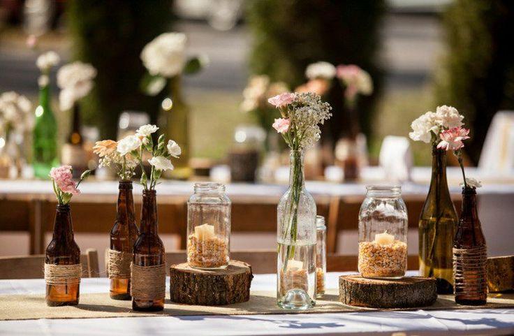 déco de table pou mariage champêtre - chemin de table en toile de jute, bouteilles-vases avec fleurs des champs sur des rondelles en bois