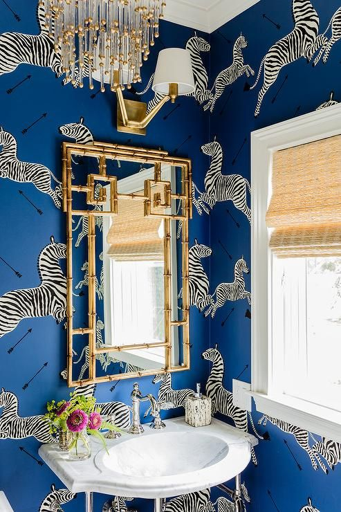 Blue powder room boasts walls clad in Scalamandre Zebra Denim Wallpaper lined with a marble wall mount sink fitted with a vintage style faucet as well as a Cyan Design Gold Bamboo Mirror illuminated by an Aerin Union Double Arm Sconce and a brass and glass chandelier.