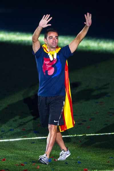 Xavi Hernandez of FC Barcelona waves during their victory parade after winning the UEFA Champions League Final at the Camp Nou Stadium on June 7, 2015 in Barcelona, Catalonia.