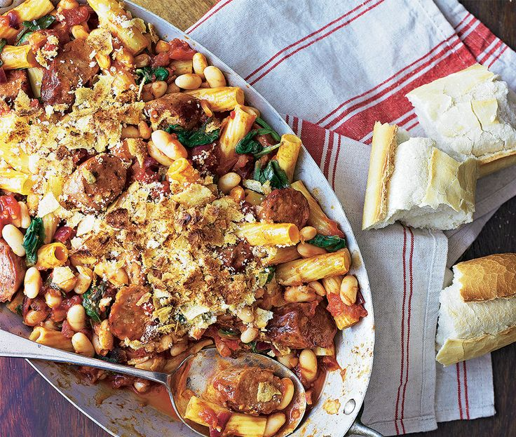 platter with sausage, rigatoni pasta, onion, tomatoes, cannelloni beans, spinach leaves and breadcrumbs with crusty bread on the side