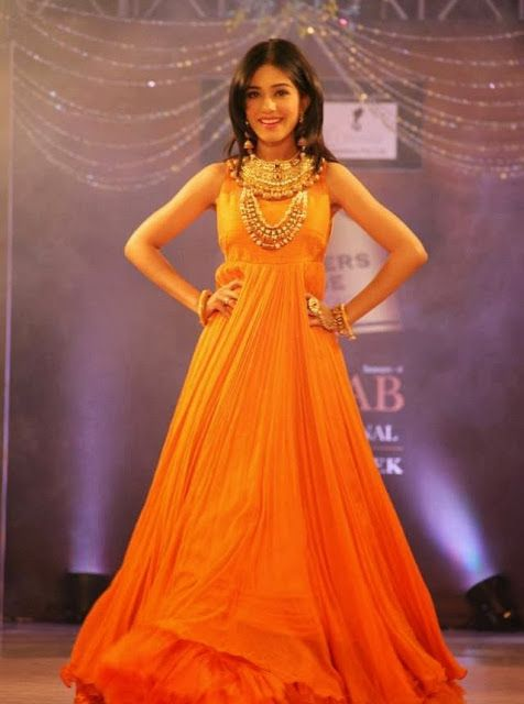 Amrita Rao walking the ramp as show stopper in an orange gown in a fashion show.