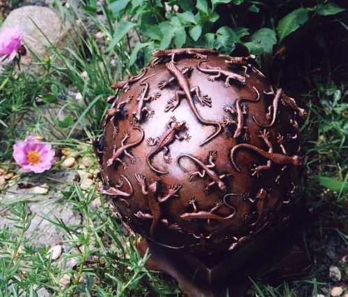 Bowling ball garden art: this look could be achieved by gluing Dollar Store creatures onto the ball and then spay painting the entire thing with a bronze paint.