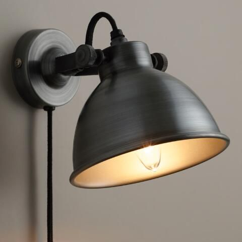 Crafted of iron with an aged zinc finish, our exclusive sconce lamp illuminates small areas without using floor space. Featuring a pivoting head, this affordable lighting solution is ideal above nightstands, reading chairs or in any dark corner. Plus, it comes complete with a textile plug-in cord for easy use without electrical installation.