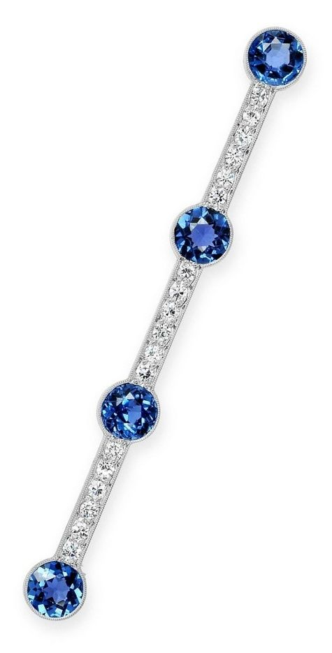 Tiffany & Co. - An Art Deco Sapphire, Diamond and Platinum Bar Brooch, circa 1930. The elongated millegrained bar decorated with a quartet of bezel-set sapphires, between rows of round diamonds, mounted in platinum, signed Tiffany & Co., and numbered.