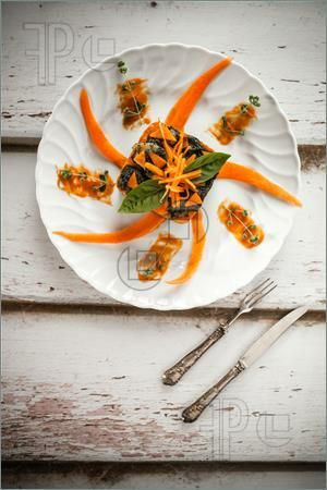 Picture of Overhead shot of plate with moulded bicolor gnocchi with pumpkin and chard cream, decorated with fresh pumpkin and basil leaves.