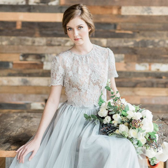 An end of winter wedding editorial juxtaposing moody dark shades with ethereal light in shades of gray with winter greenery and a crop top wedding dress!