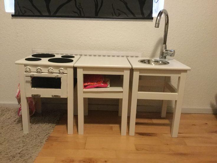 Legekøkken af Ikea Oddvar taburetter. Der er sat sort hylde i komfuret. Ovn lågen er lavet af 2 udskårne plader med plexiglas imellem. Kogeplader af sort filt. Hvid hylde i midtermodulet. Hundefoderskål som køkkenvask. Gammel vandhane.