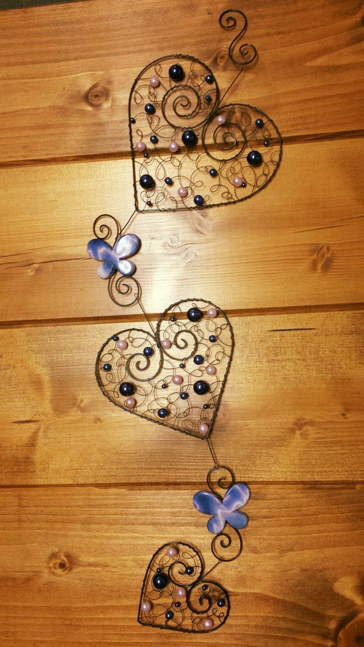 Závěsná dekorace srdce Závěsná dekorace 3 srdce je vyrobena z černého žíhaného drátu a ozdobena růžovými a fialovými korálky a motýlky. Délka celého závěsu 50 cm.