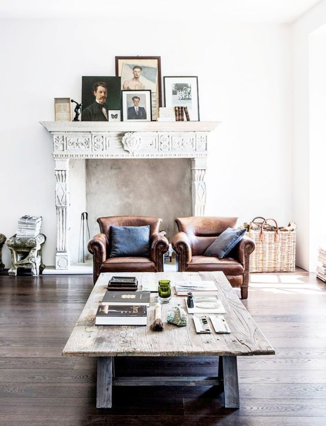 Painted mantel with framed photos and a pair of leather chairs